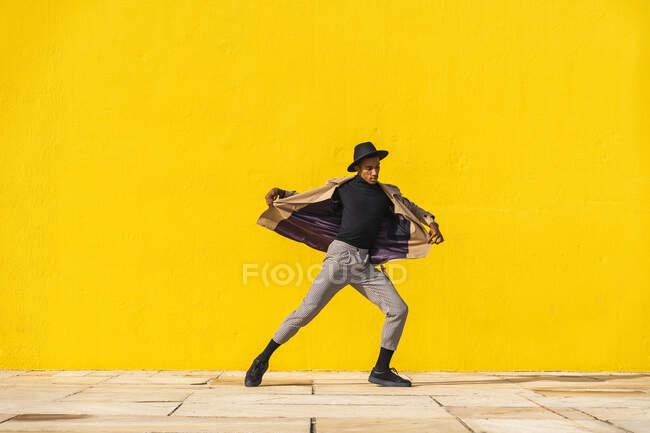 Joven bailando frente a la pared amarilla - foto de stock