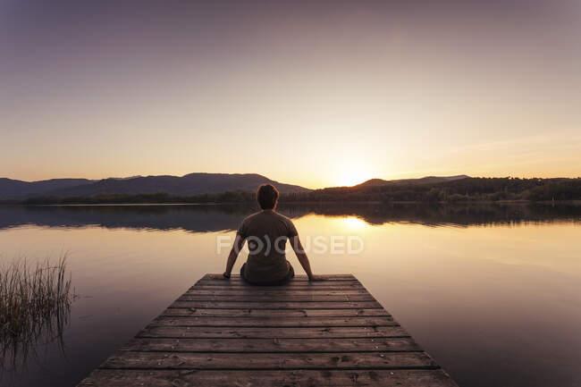 Silhouette di un uomo seduto su una passerella di legno al tramonto — Foto stock
