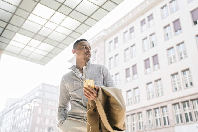 Portrait of businessman using earphones and smartphone in the city — Stock Photo