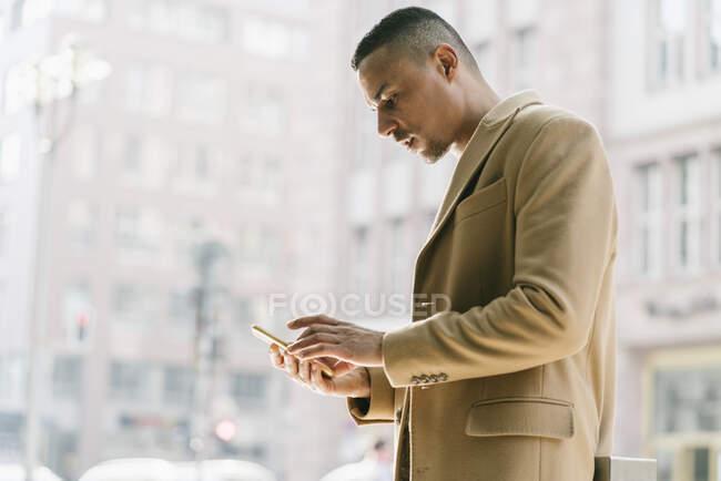 Retrato del hombre de negocios mirando el teléfono inteligente - foto de stock
