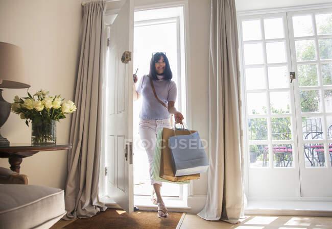 Mujer con bolsas de compras, entrando por la puerta principal - foto de stock