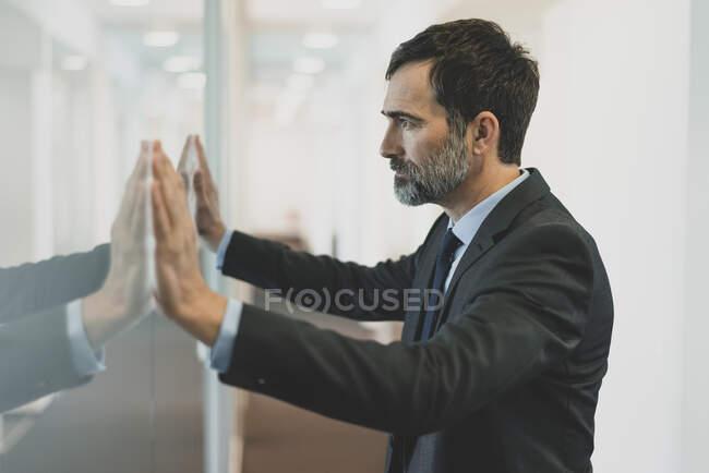 Pensativo homem de negócios maduro encostado à parede de vidro no escritório — Fotografia de Stock