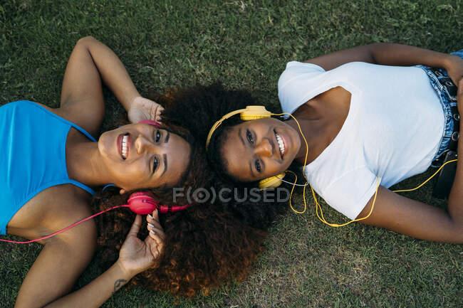 Retrato de duas jovens mulheres felizes deitadas no prado ouvindo música com fones de ouvido — Fotografia de Stock