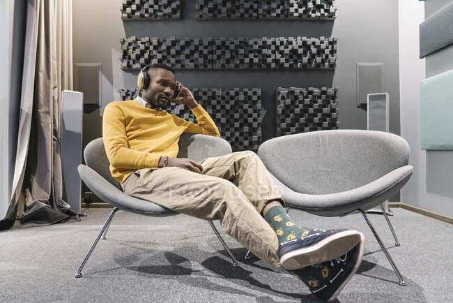 Людина з навушниками сидить у кріслі — стокове фото