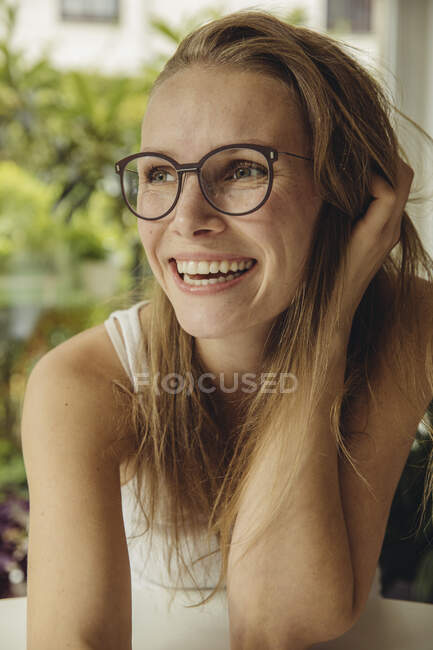 Portrait of happy young woman with glasses looking sideways — Stock Photo