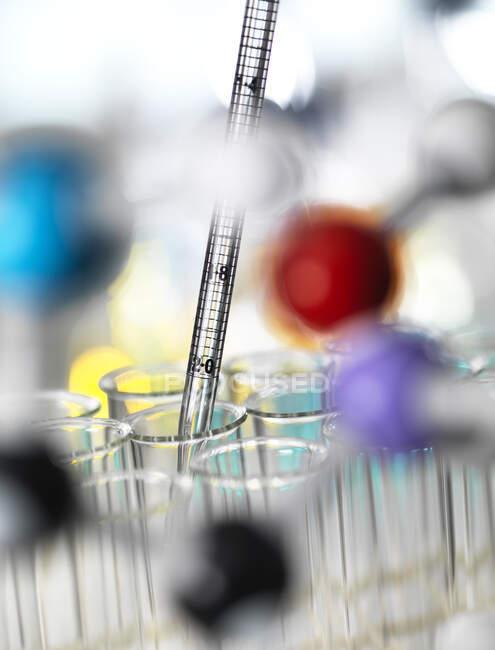 Gros plan sur le pipetage d'échantillons chimiques dans des éprouvettes pour expérimentation en laboratoire — Photo de stock