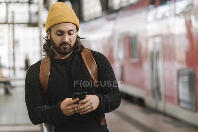 Молодий чоловік користується смартфоном на станції (Берлін, Німеччина). — стокове фото