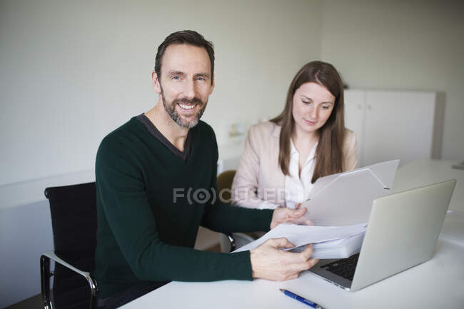 Portrait of smiling businessman and employee working at desk in office — Stock Photo