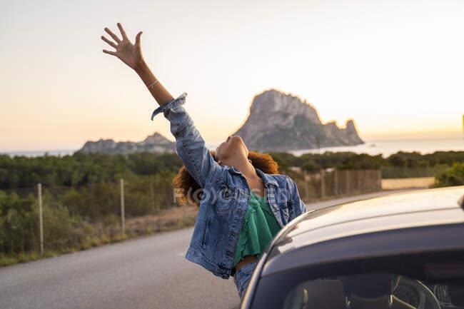 Giovane donna durante il viaggio su strada con braccio sollevato — Foto stock