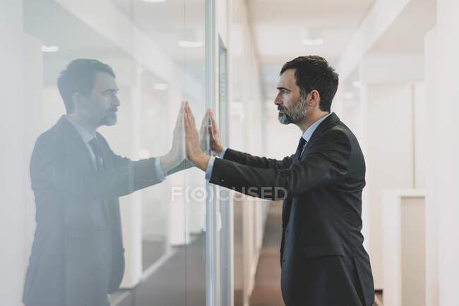 Homme d'affaires mûr réfléchi appuyé contre le mur de verre dans le bureau — Photo de stock