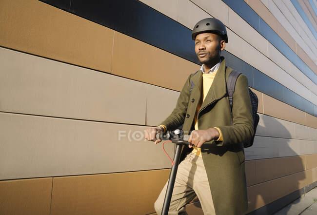 Homme élégant avec casque et scooter dans un bâtiment — Photo de stock