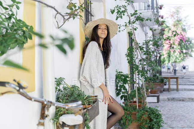 Молода жінка в сонцезахисному капелюсі і кардиган спираючись на стіну. — стокове фото