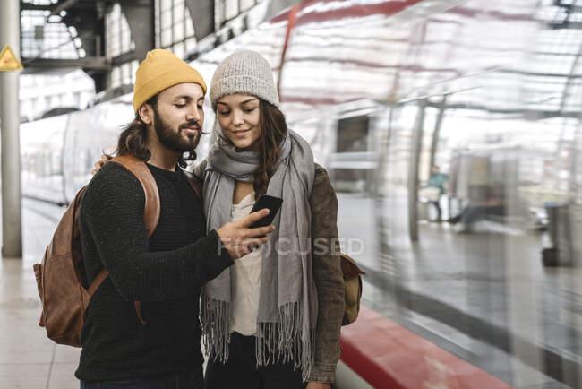 Jovem casal usando smartphone na plataforma da estação como o trem entra, Berlim, Alemanha — Fotografia de Stock