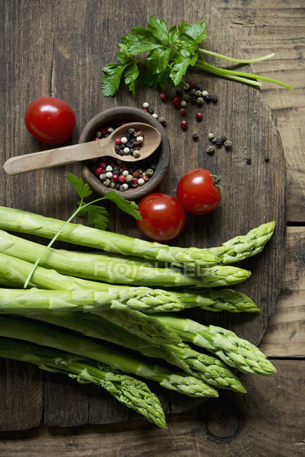 Overhead view of green asparagus, tomatoes, parsley and colored pepper on wooden cutting board — Stock Photo