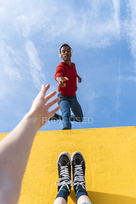 Young man with headphones, dancing for person, leaning on yellow wall — Stock Photo