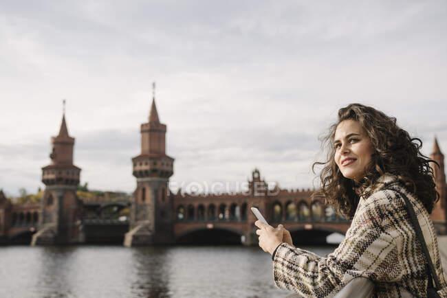 Усміхнена жінка зі смартфоном у місті на мості Обербаум (Берлін, Німеччина). — стокове фото