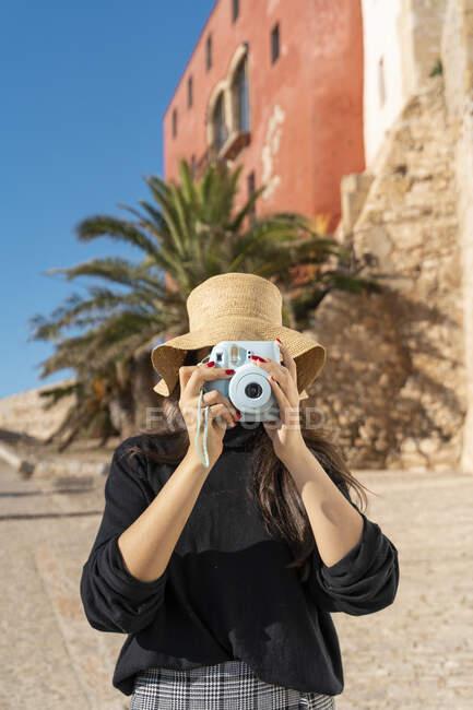Retrato de una joven morena fotografiando con una cámara azul - foto de stock