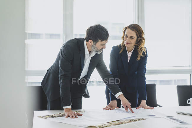 Businesswoman and businessman working on plan on desk in office — Stock Photo