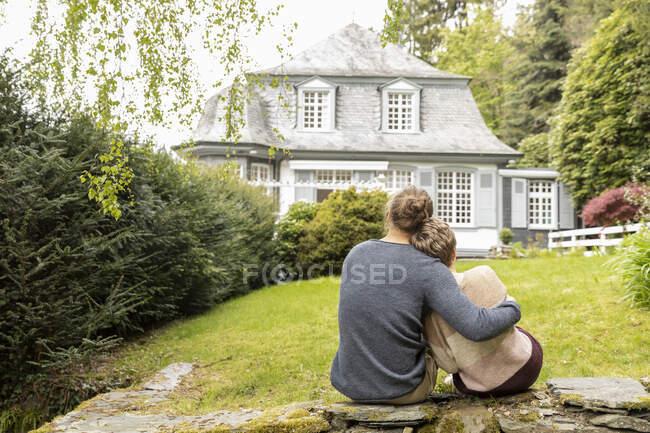 Вид сзади пары, сидящей на стене в саду — стоковое фото