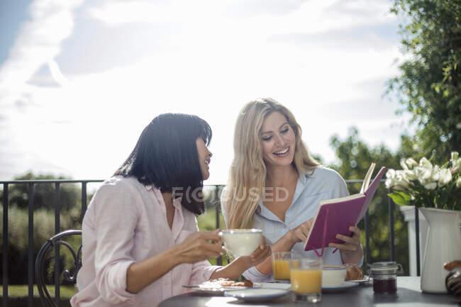 Deux femmes prenant le petit déjeuner à la table de café extérieure, livre de lecture — Photo de stock