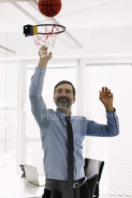 Счастливый зрелый бизнесмен играет в баскетбол в офисе — стоковое фото