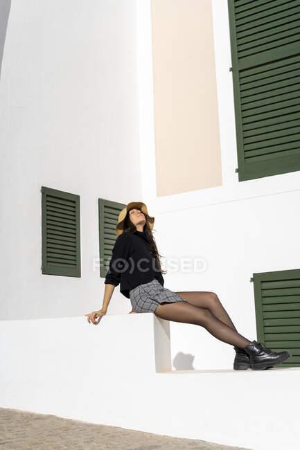 Young brunette woman sitting on white wall, enjoying sunlight — Stock Photo