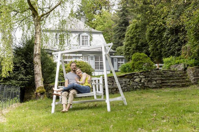 Расслабленная пара в саду своего дома — стоковое фото