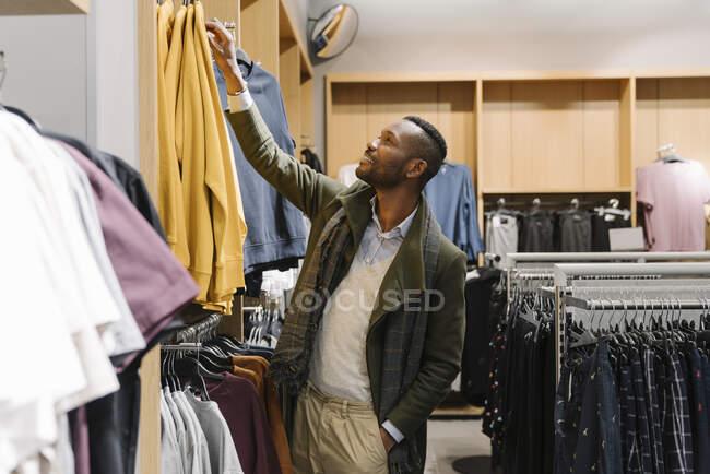 Elegante homem compras em uma loja de roupas — Fotografia de Stock