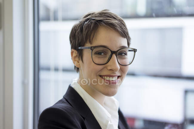 Portait of smiling young businesswoman at the window — Stock Photo