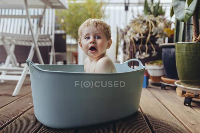 Малыш сидит в детской ванне на балконе — стоковое фото