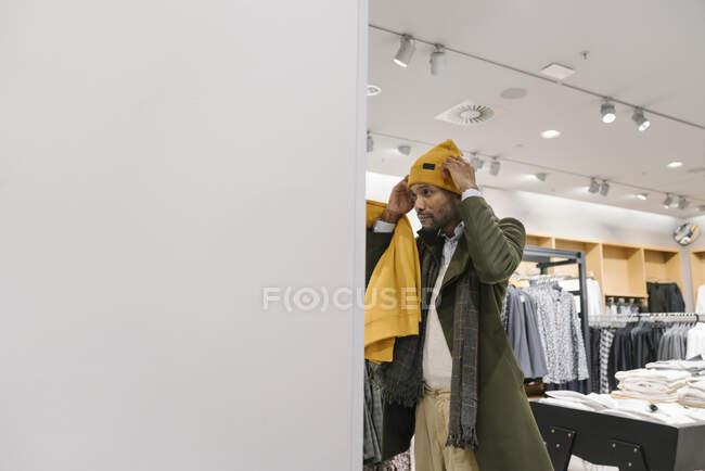 Тихий чоловік купує речі в магазині одягу, намагаючись покуштувати боби. — стокове фото