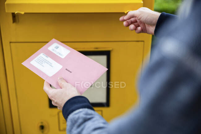 Elector holding documtents for the postal vote in front of the mailbox — Stock Photo