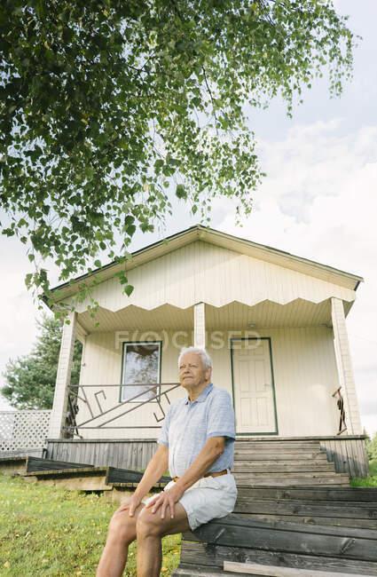 Ritratto di uomo anziano che si rilassa davanti alla casa vacanze, Kalvene Lettonia — Foto stock