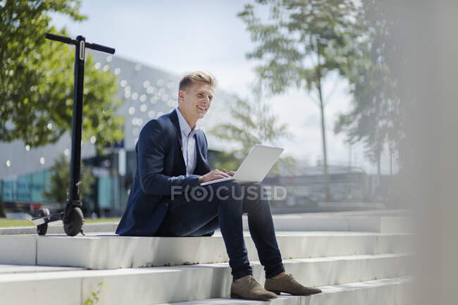 Young businessman with e-scooter using laptop in the city — Stock Photo