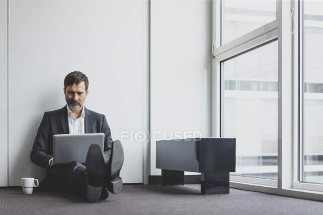 Homme d'affaires mature dans le bureau assis sur le sol en utilisant un ordinateur portable — Photo de stock