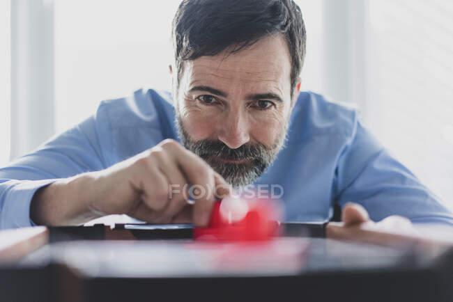 Retrato de un hombre de negocios maduro jugando hockey sobre aire - foto de stock