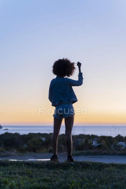 Veduta posteriore della giovane donna con la mano nei capelli in piedi su un punto di vista al tramonto, Ibiza — Foto stock