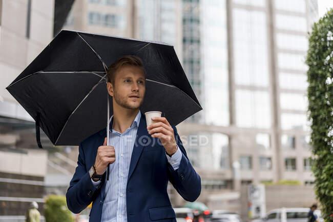Jeune homme d'affaires avec parapluie buvant un café pendant une journée pluvieuse à Bangkok — Photo de stock