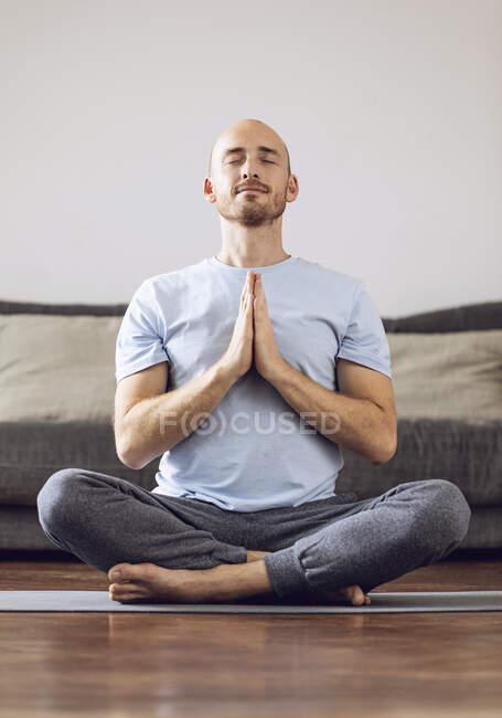 Man doing yoga at home — Stock Photo