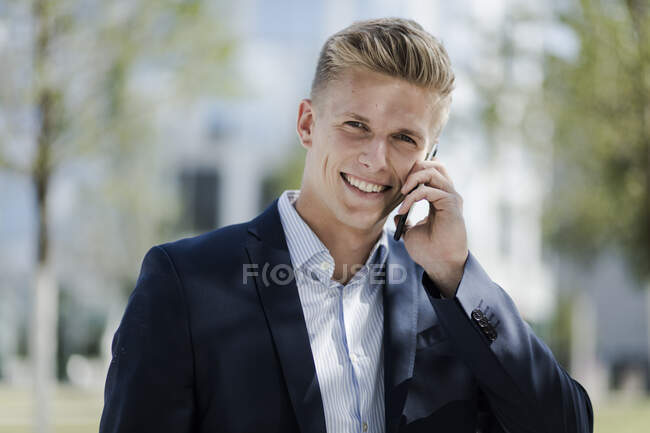 Portrait of smiling young businessman talking on cell phone — Stock Photo