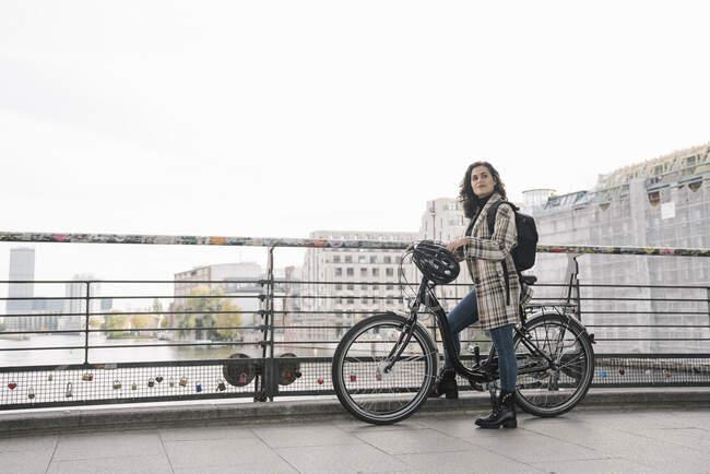 Donna con una bicicletta in piedi su un ponte in città, Berlino, Germania — Foto stock