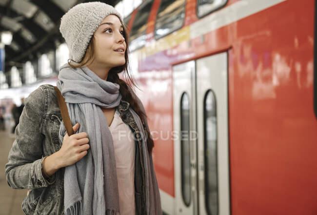 Mujer joven en el andén de la estación cuando llega el tren, Berlín, Alemania - foto de stock