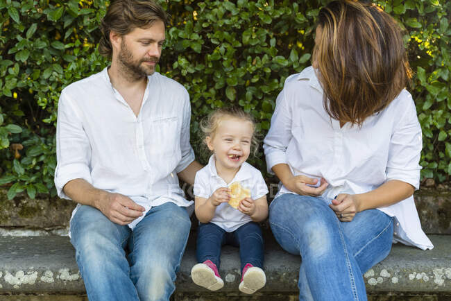 Parents avec une petite fille heureuse assis sur un banc — Photo de stock