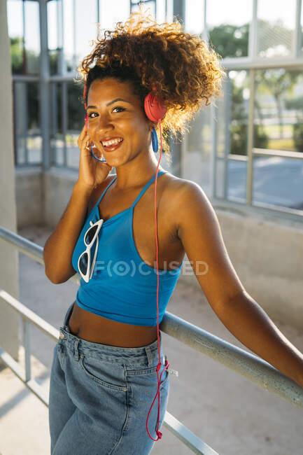 Retrato de uma jovem sorridente ouvindo música com fones de ouvido — Fotografia de Stock