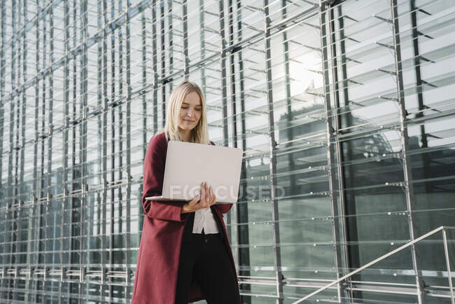 Біла комерсантка з ноутбуком на задньому плані сучасного офісного будинку. — стокове фото