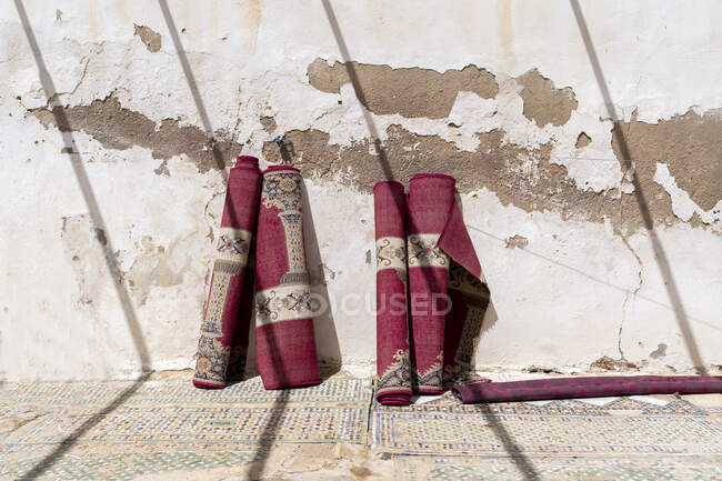 Four rolled up carpets leaning against wall at sunlight, Fez, Morocco — Stock Photo