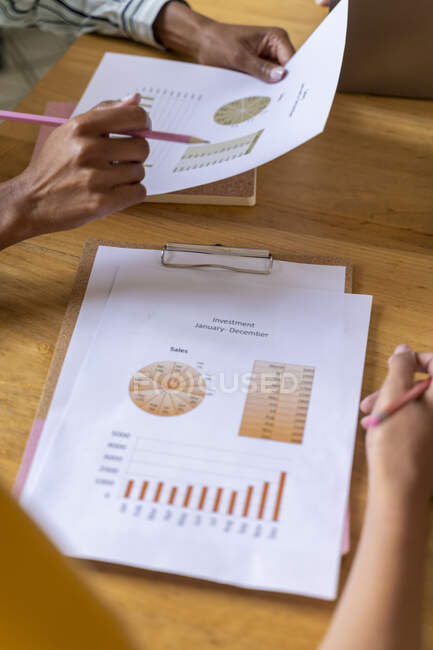 Close-up of businesswomen having a meeting in office analyzing charts — Stock Photo
