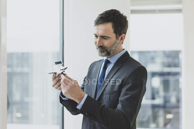 Smiling mature bussinessman holding space shuttle model — Stock Photo