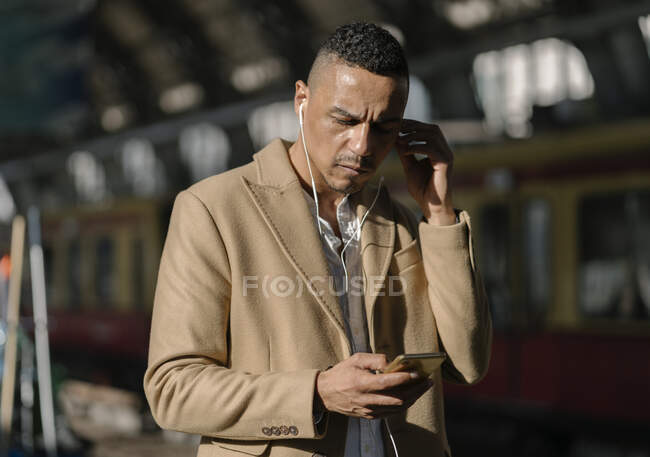 Businessman at train station Alexanderplatz using earbuds and smartphone, Berlin, Germany — Stock Photo