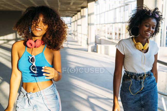 Retrato de dos mujeres jóvenes con auriculares al atardecer - foto de stock